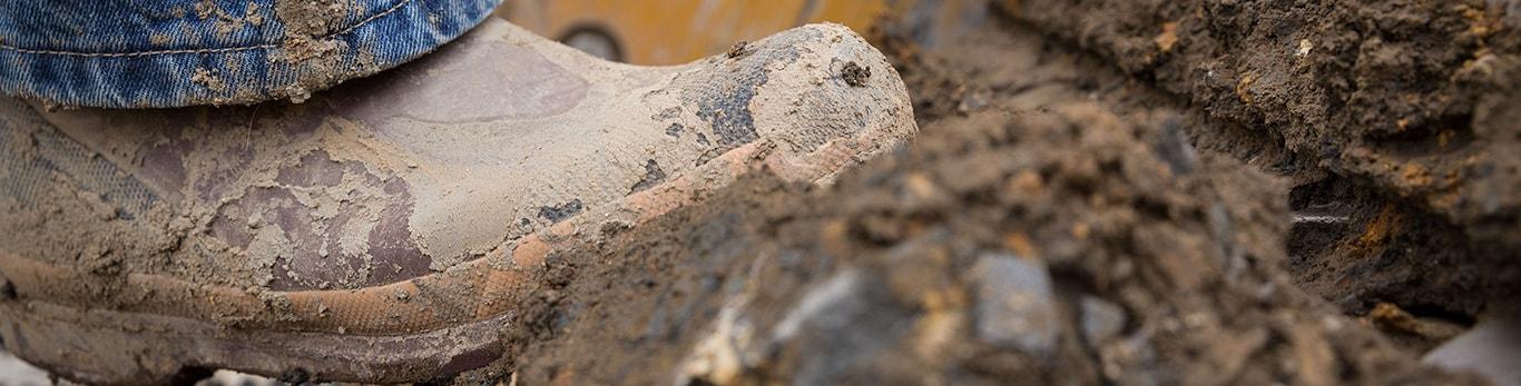 Botas cubiertas de lodo que avanzan